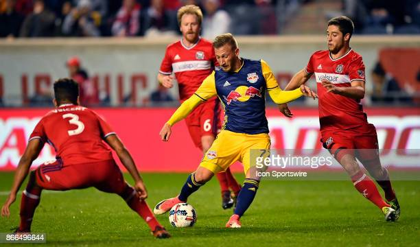 New York Red Bulls midfielder Daniel Royer kicks the ball between Chicago Fire defender Brandon Vincent and Chicago Fire defender Matt Polster to...