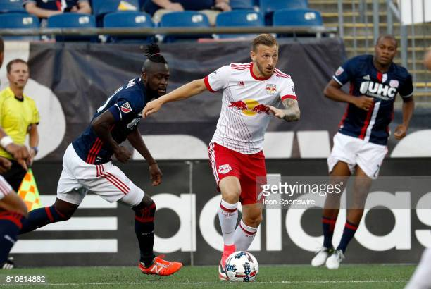 New York Red Bulls midfielder Daniel Royer looks to pass watched by New England Revolution forward Kei Kamara during a regular season MLS match...