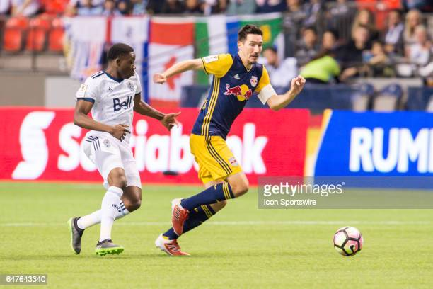New York Red Bulls midfielder Sacha Kljestan is pursued by Vancouver Whitecaps forward Alphonso Davies during the CONCACAF Champions League...