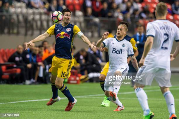 New York Red Bulls midfielder Sacha Kljestan plays the ball off his chest as he's pursued by Vancouver Whitecaps midfielder Andrew Jacobson during...