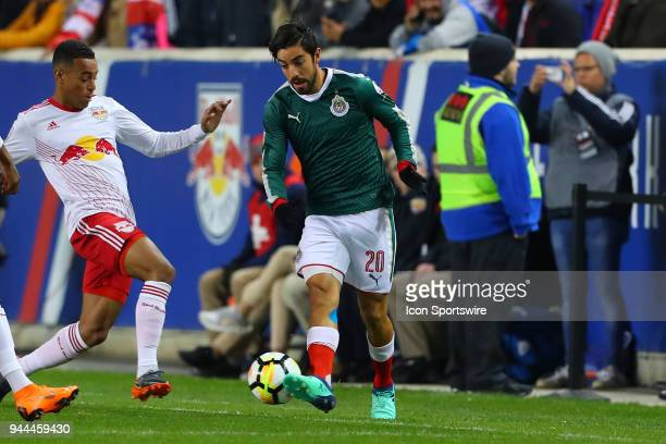 New York Red Bulls midfielder Tyler Adams battles Guadalajara midfielder Rodolfo Pizarro during the first half of the CONCACAF Champions League game...