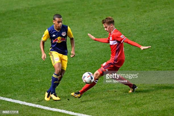 New York Red Bulls midfielder Tyler Adams is defended by Chicago Fire midfielder Djordje Mihailovic during the MLS Cup Playoff match between the New...