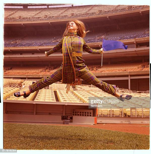 Ruth Ryan shows how she feels about the World's Champion Mets and her husband Nolan's pitching as she leaps into the air modeling knit pants suit...