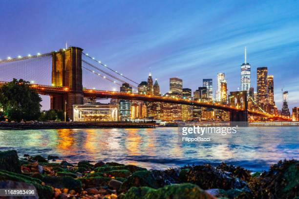 new york skyline at night with brooklyn bridge - brooklyn bridge stock pictures, royalty-free photos & images