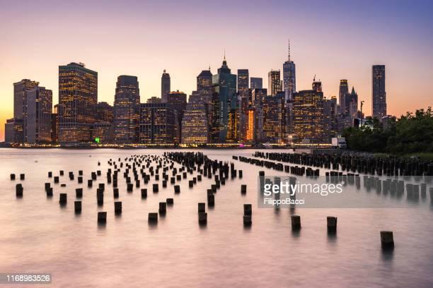 new york skyline bei sonnenuntergang - brooklyn bridge park stock-fotos und bilder
