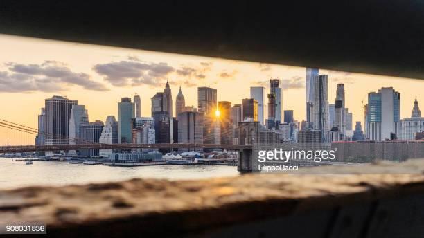new york city skyline bei sonnenuntergang - brooklyn bridge park stock-fotos und bilder