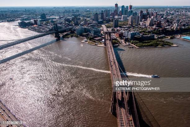 new york skyline with the two bridges, brooklyn bridge and manhattan bridge crossing the east river, taken from a helicopter above brooklyn, overlooking the manhattan side. some ships are passing below the bridges - madison avenue stock pictures, royalty-free photos & images