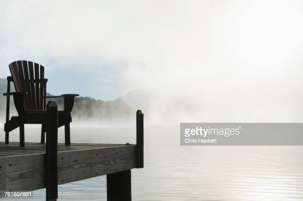 USA, New York, St Armand, Empty chair on jetty by Lake Placid at dawn