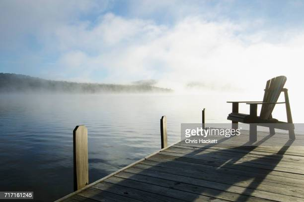 USA, New York, St. Armand, Lake Placid, Outdoor chair on pier by lake