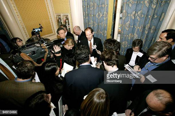 New York State Attorney General Eliot Spitzer center speaks to reporters after a speech at the Kroll International Seminar in New York January 13 2004