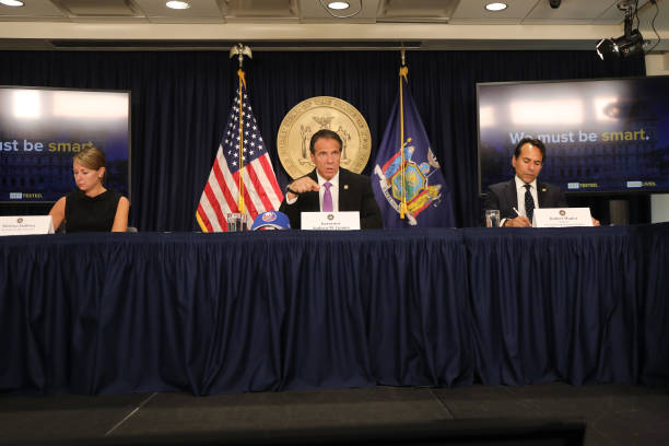 New York state Gov Andrew Cuomo flanked by Melissa DeRosa secretary to the governor and state Budget Director Robert Mujica speaks at a news...