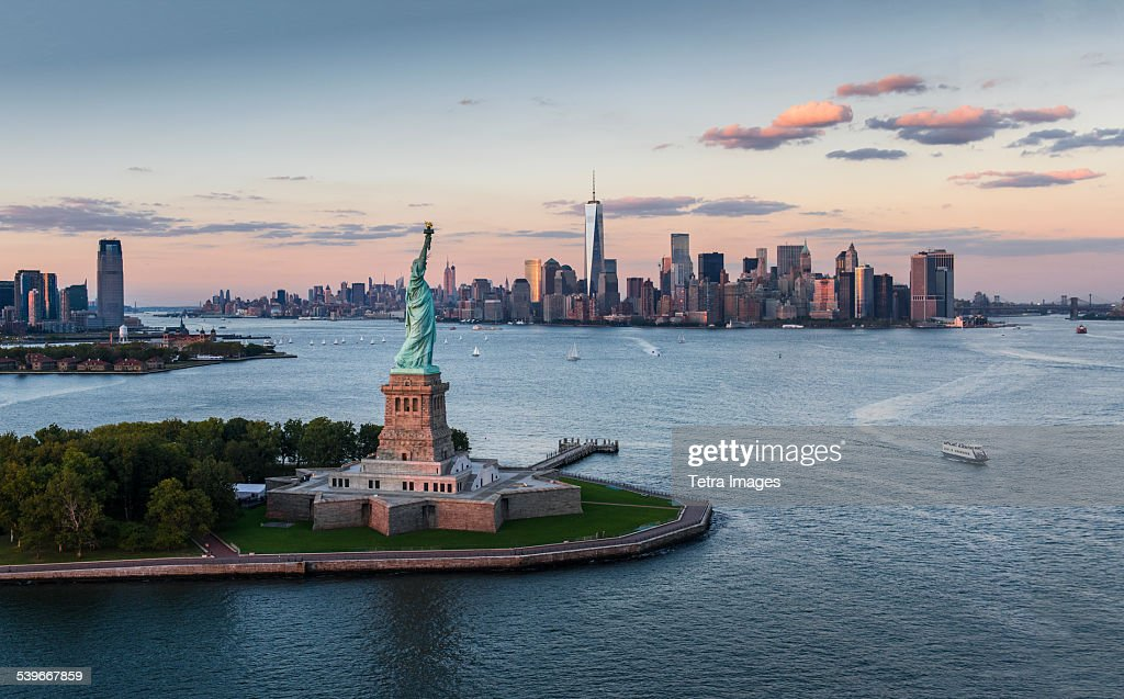 USA, New York State, New York City, Aerial view of city with Statue of Liberty at sunset : Stock Photo