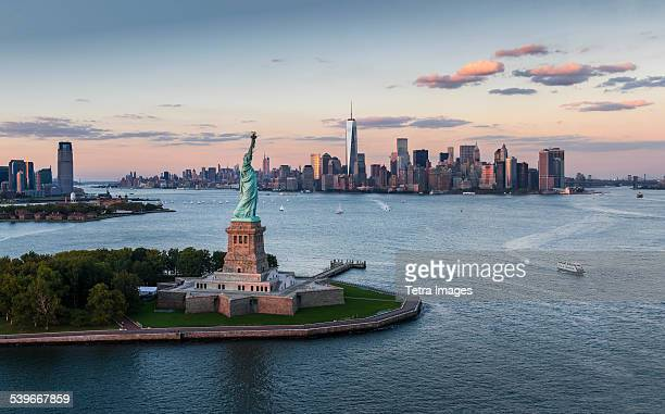 usa, new york state, new york city, aerial view of city with statue of liberty at sunset - lower manhattan stock photos and pictures
