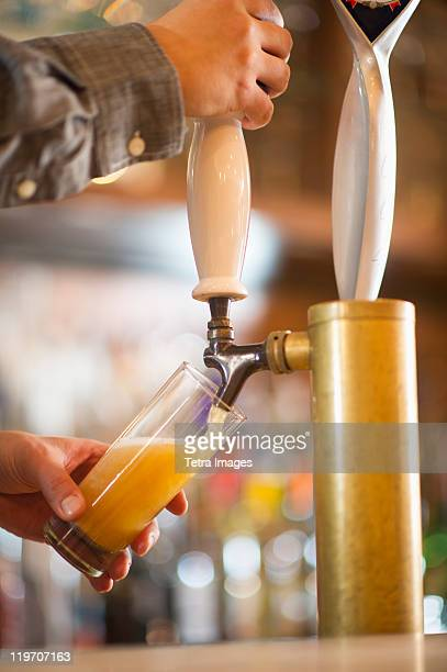 USA, New York State, New York City, Barman poring beer from beer tap