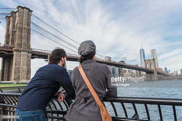 USA, New York State, New York City, Brooklyn, Couple leaning against railing and looking at Freedom Tower