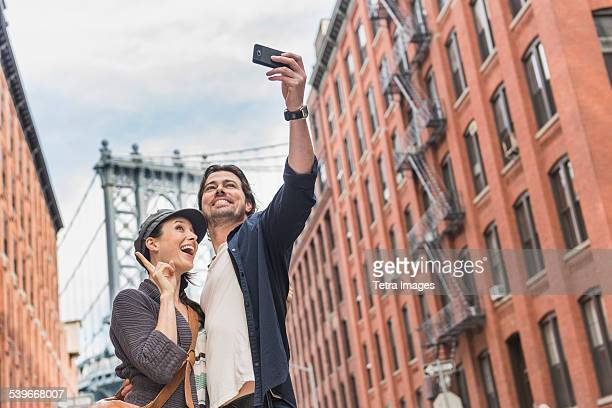 USA, New York State, New York City, Brooklyn, Couple taking selfie on street, Brooklyn Bridge in background