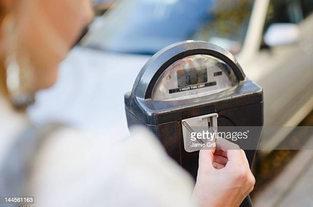 usa, new york state, new york city, brooklyn, woman inserting coin into parking meter - parking meter stock photos and pictures