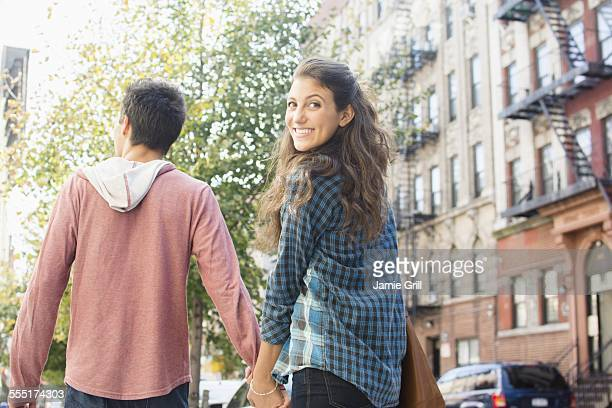 USA, New York State, New York City, Brooklyn, Young couple holding hands on sidewalk