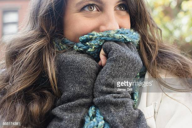 USA, New York State, New York City, Brooklyn, Young woman hiding her face behind scarf