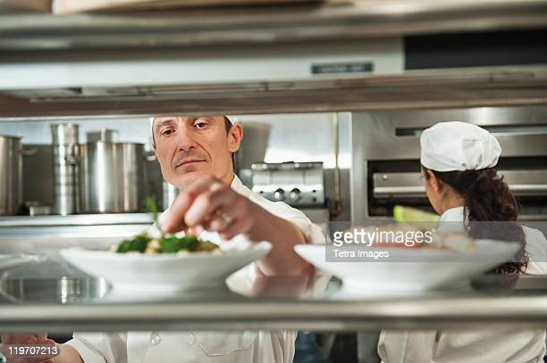 USA, New York State, New York City, Chefs preparing food in kitchen