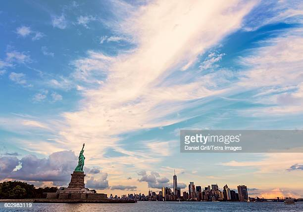 USA, New York State, New York City, Manhattan, Statue of Liberty and financial district at dusk