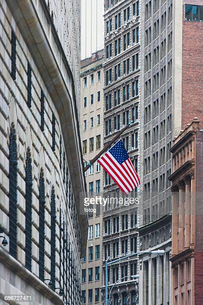 USA, New York State, New York City, Manhattan, Wall Street, American flag among skyscrapers