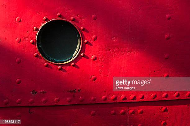 USA, New York State, New York City, Porthole of red nautical vessel