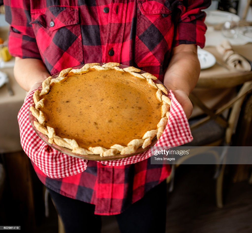 USA, New York State, New York City, Woman holding baked pumpkin pie for Thanksgiving : Stock Photo