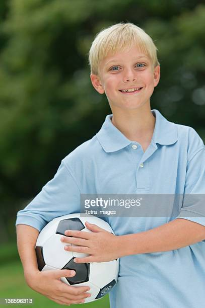 USA, New York State, Old Westbury, Boy (10-11) holding soccer ball