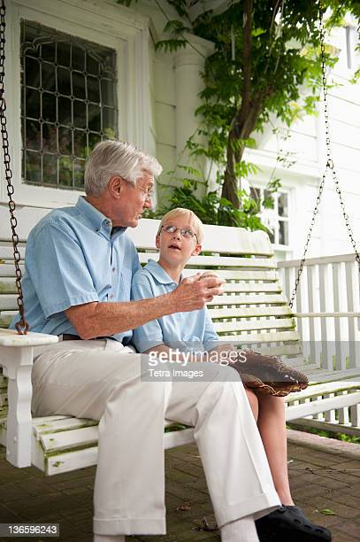USA, New York State, Old Westbury, Grandfather and grandson (10-11) sitting on porch swing