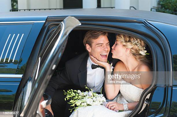 USA, New York State, Old Westbury, Newly wed couple sitting in limousine