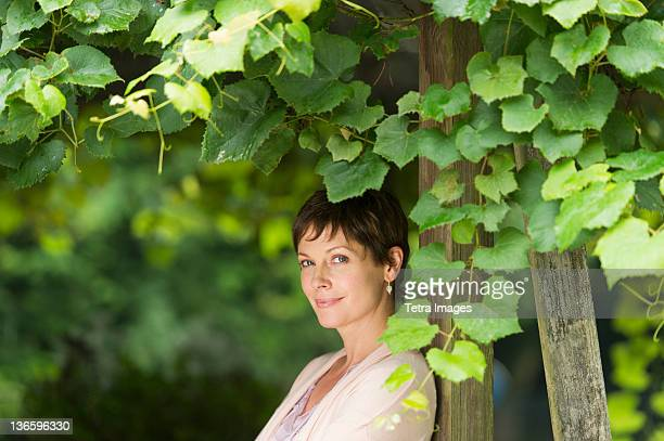 usa, new york state, old westbury, portrait of mature woman leaning against wooden post overgrown with ivy - einzelne frau über 40 stock-fotos und bilder