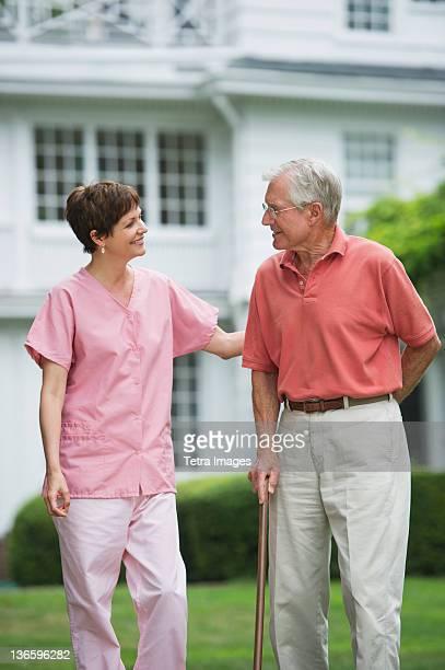 USA, New York State, Old Westbury, Senior man and nursing assistant walking in back yard