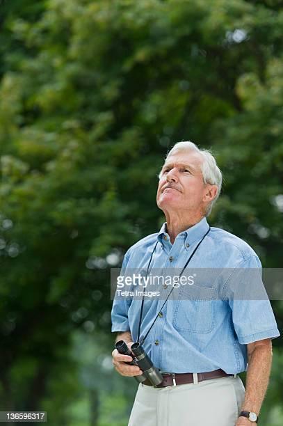 USA, New York State, Old Westbury, Senior man with binoculars