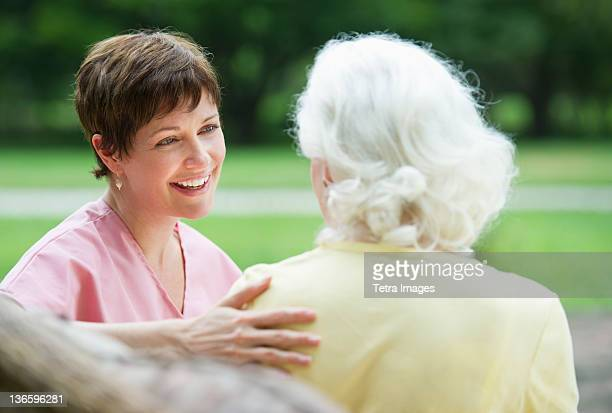 usa, new york state, old westbury, senior woman and nursing assistant relaxing on outdoor sofa - nursing assistant - fotografias e filmes do acervo