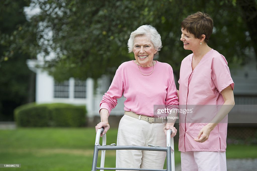 USA, New York State, Old Westbury, Senior woman walking with walker with help of nursing assistant : Stock Photo