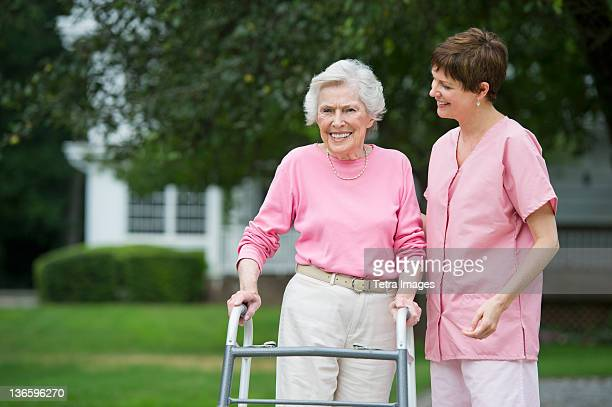 usa, new york state, old westbury, senior woman walking with walker with help of nursing assistant - nursing assistant fotografías e imágenes de stock