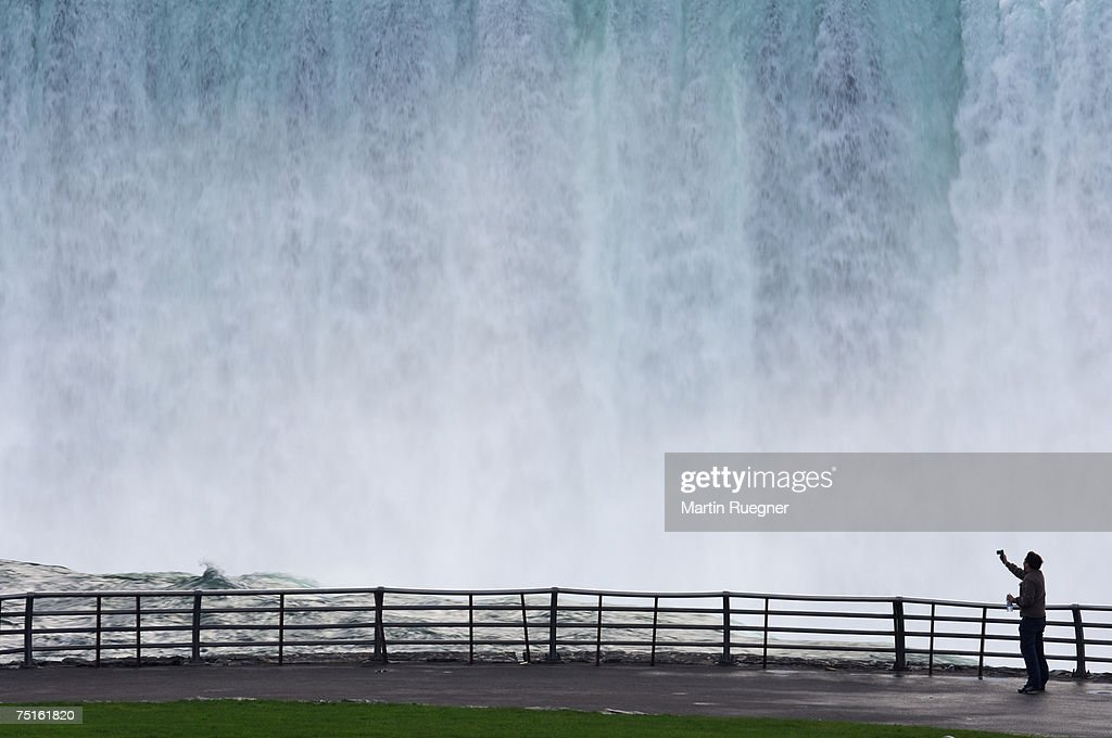 USA, New York State, Ontario, Niagara Falls, man photographing waterfall : Stock Photo
