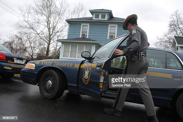 New York state police officer walks out of the home of Linh Voong, who is believed to have killed 13 people in an immigration community center...