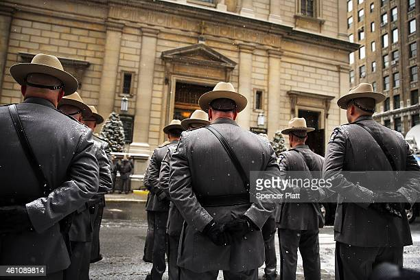 New York State Police wait for the hearse carrying the casket of former threeterm governor Mario Cuomo out of St Ignatius Loyola Church on January 6...