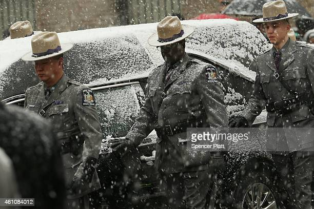 New York State Police walk with the hearse carrying the casket of former threeterm governor Mario Cuomo into St Ignatius Loyola Church on January 6...