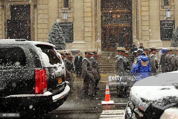New York State Police walk with the hearse carrying the casket of former threeterm governor Mario Cuomo out of St Ignatius Loyola Church on January 6...