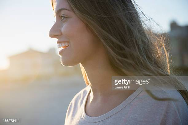 USA, New York State, Rockaway Beach, Profile of smiling woman at sunset