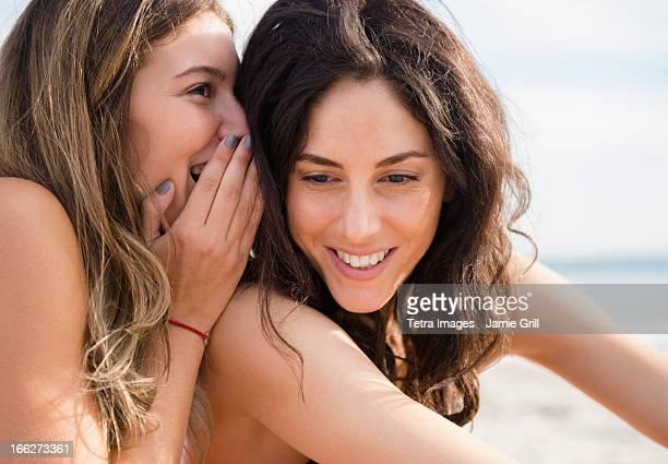 usa, new york state, rockaway beach, two women whispering on beach - weibliche freundschaft stock-fotos und bilder