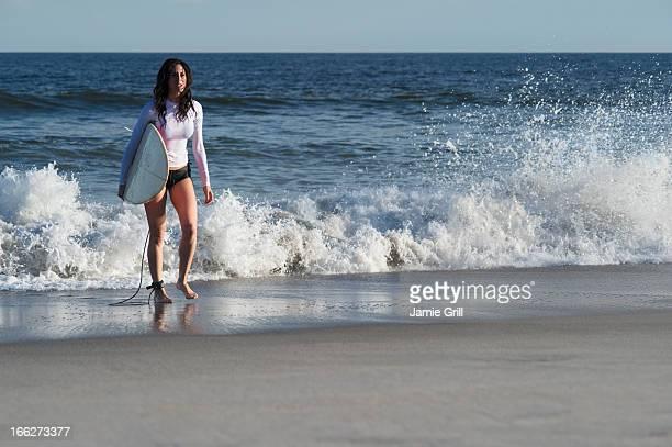 usa, new york state, rockaway beach, woman carrying surfboard on beach - halbinsel rockaway peninsula stock-fotos und bilder