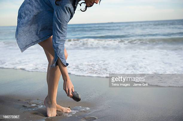 usa, new york state, rockaway beach, woman collecting seashells on beach - tunic stock pictures, royalty-free photos & images