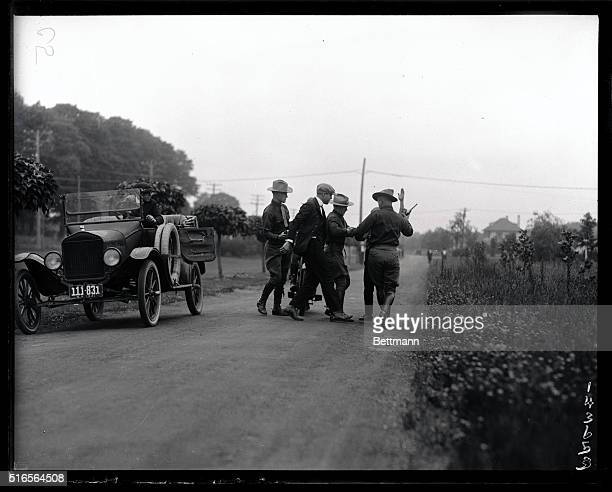 New York State Troopers are shown arresting a bootlegger in the middle of a road in New York.