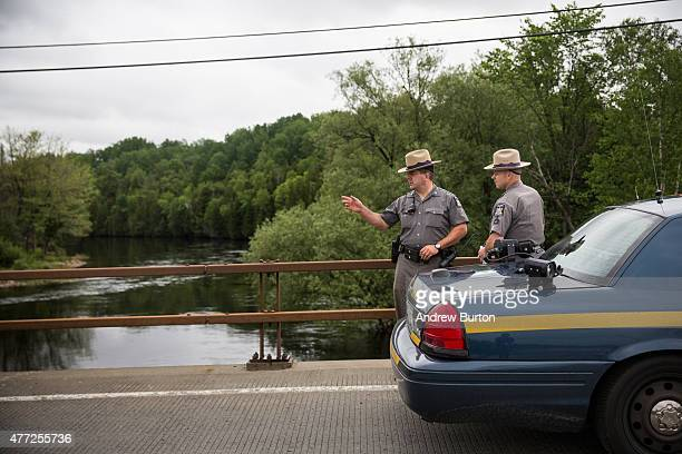 New York State Troopers hold a meeting while searching for two escaped convicts on June 15, 2015 outside Dannemora, New York. The two convicted...