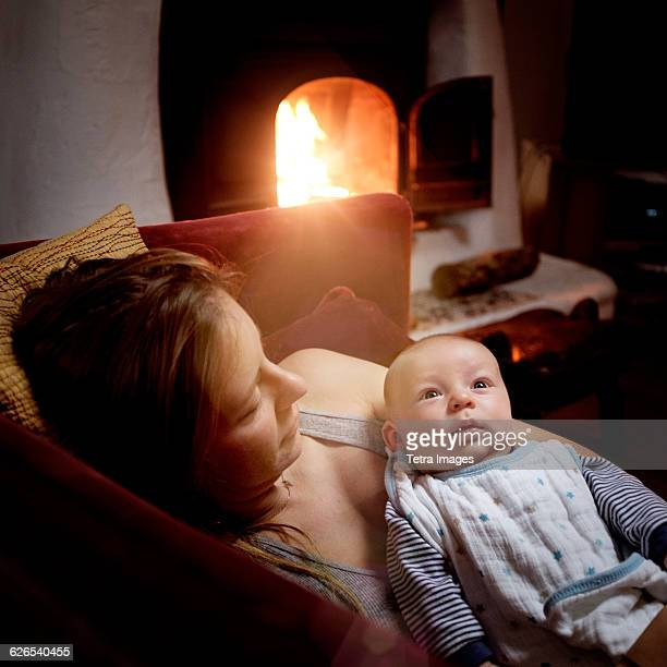USA, New York State, Woodstock, Woman resting with baby girl (2-5 months) on sofa