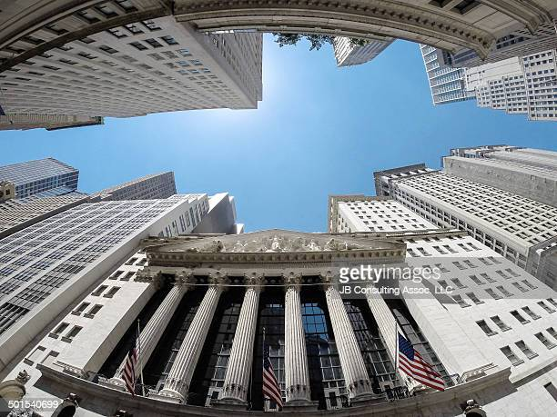 New York Stock Exchange located at the corner or Wall Street & Broad Street. Upward angle using a super wide angle lens. Beautiful sunny day with...